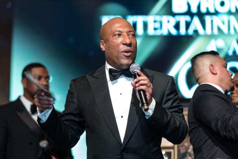Byron Allen wearing a tuxedo and holding a microphone while speaking on stage at a charity event.