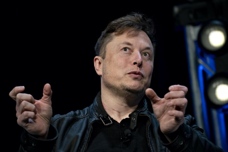 SpaceX CEO Elon Musk gesturing with his hands and speaking during a conference.