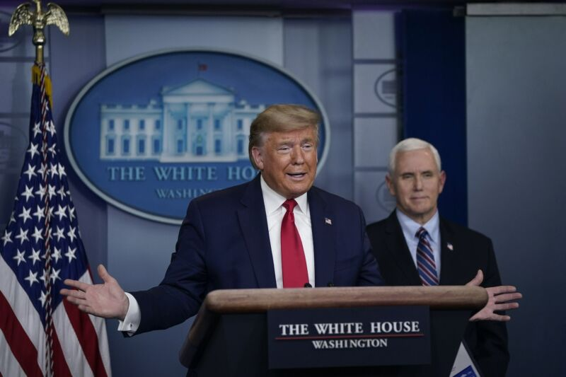 President Trump speaking in front of a podium at a daily briefing.