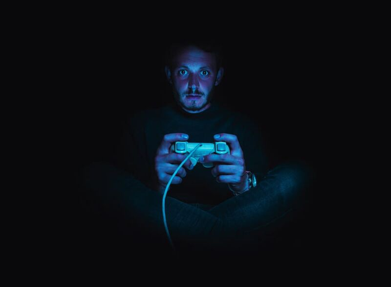 Stock photo of a man playing video games in the dark.