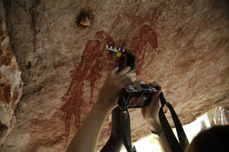 A camera is held up to ancient rock art.