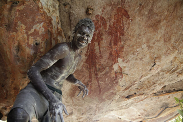 Ado French, from one of the families of local Traditional Owners, in front of a pair of Gwion rock art figures.