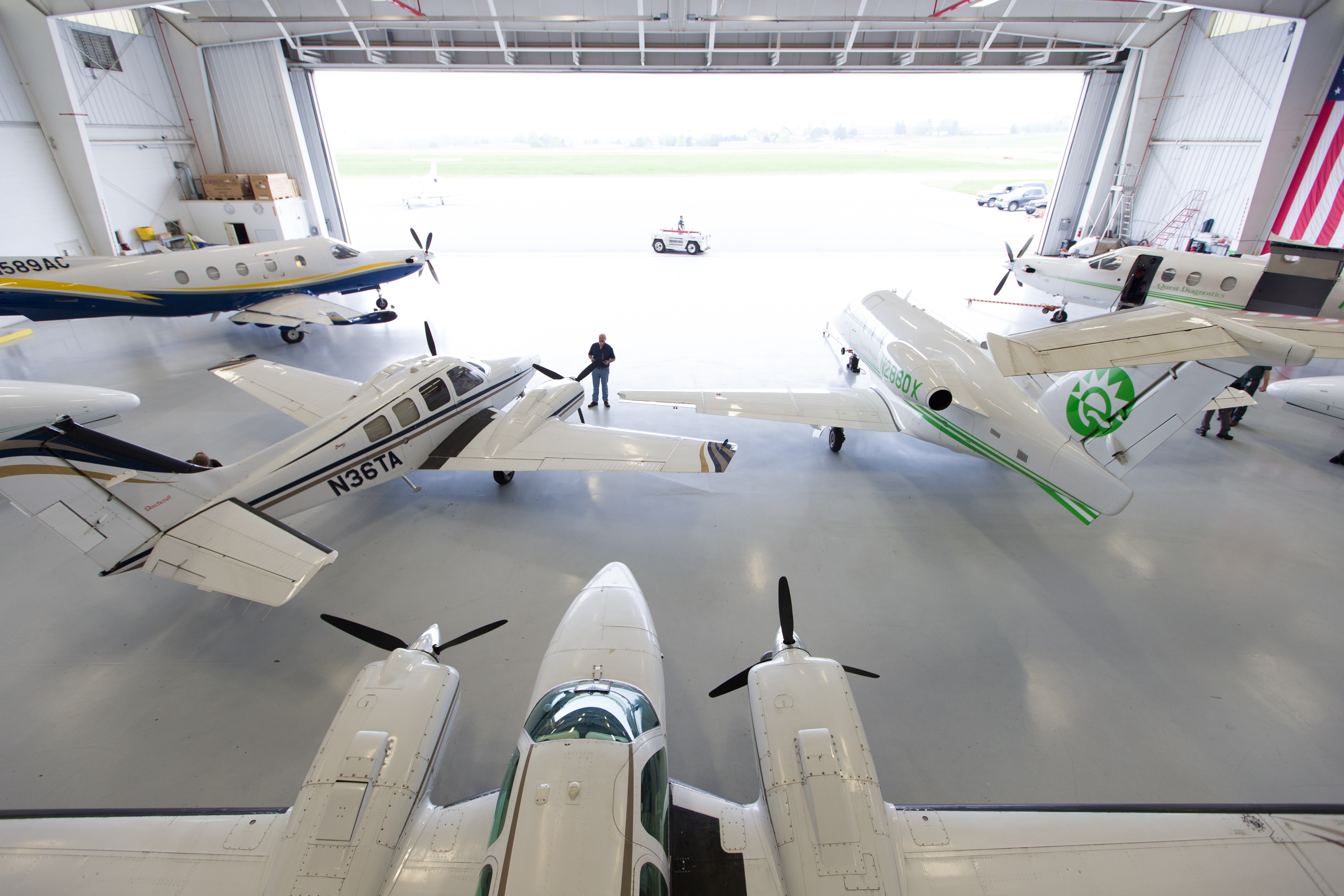 All three airplane types currently flown by Quest Diagnostics awaiting a night's work in the hangar. PC-12s sit forward at left and right by the door. Beech Barons are in the foreground at left and center. An Embraer Phenom 100 is in the foreground on the right.