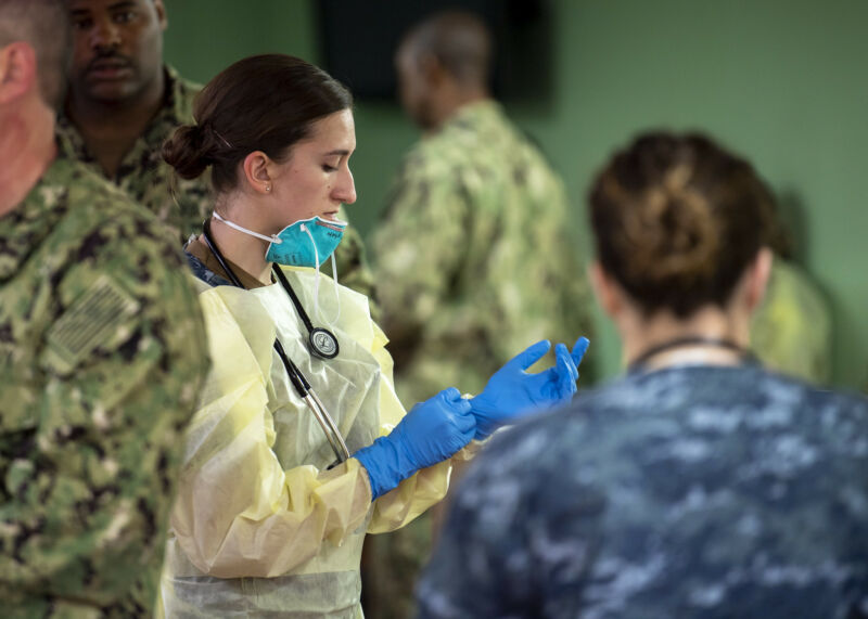 Hospital Corpsman 3rd Class Kimberly Wyss, from Ventura, Calif., dons surgical gloves aboard the hospital ship USNS <em>Mercy </em>(T-AH 19).