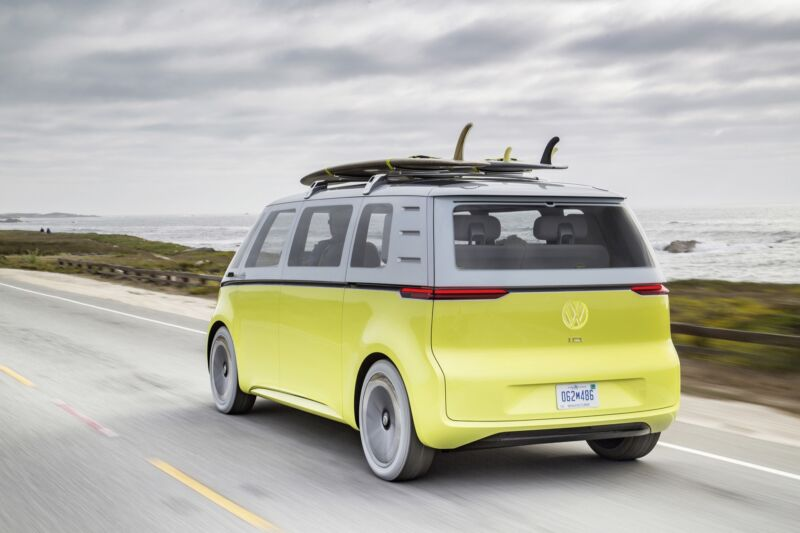 A yellow VW bus concept car drives through the beach with a surfboard on the roof.