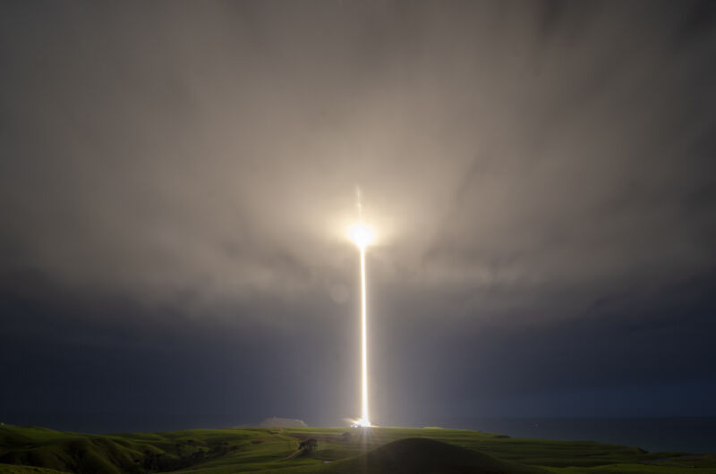 A rocket leaves a trail of light and fire as it lifts into the clouds.