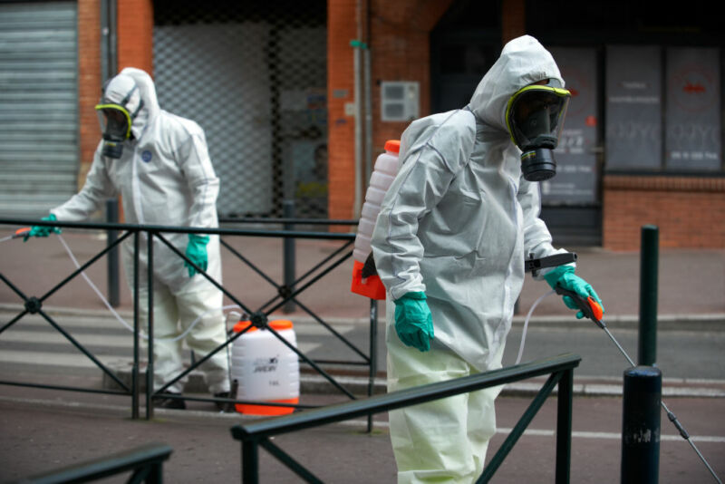 Image of two men in protective clothing spraying a public area.