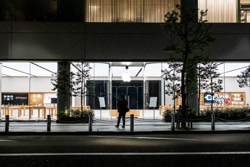 A man stands in front of a closed Apple Store in Tokyo.