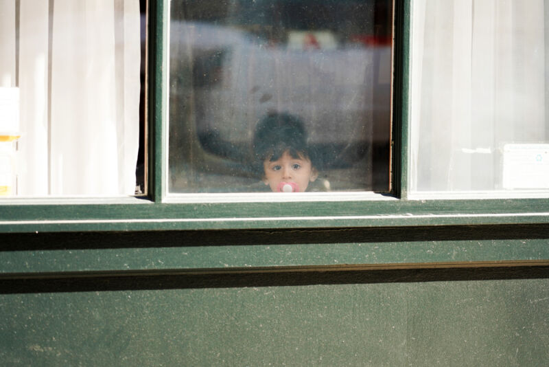 NEW YORK, NEW YORK - MARCH 24:  A child with a pacifier looks out a window as the coronavirus continues to spread across the United States on March 24, 2020 in New York City. The World Health Organization declared COVID-19 a global pandemic on March 11th. (Photo by Cindy Ord/Getty Images)