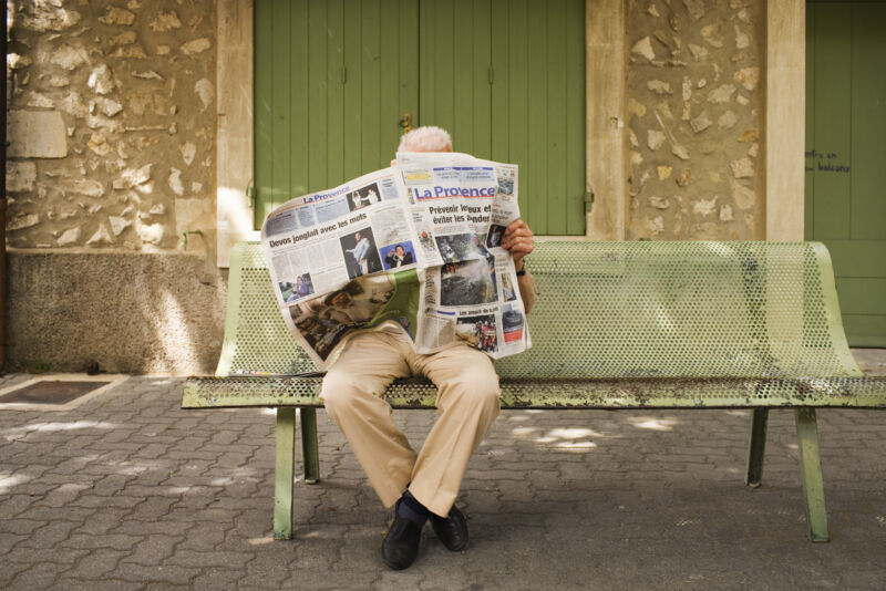 Photograph of a man sitting on a park bench reading a newspaper.