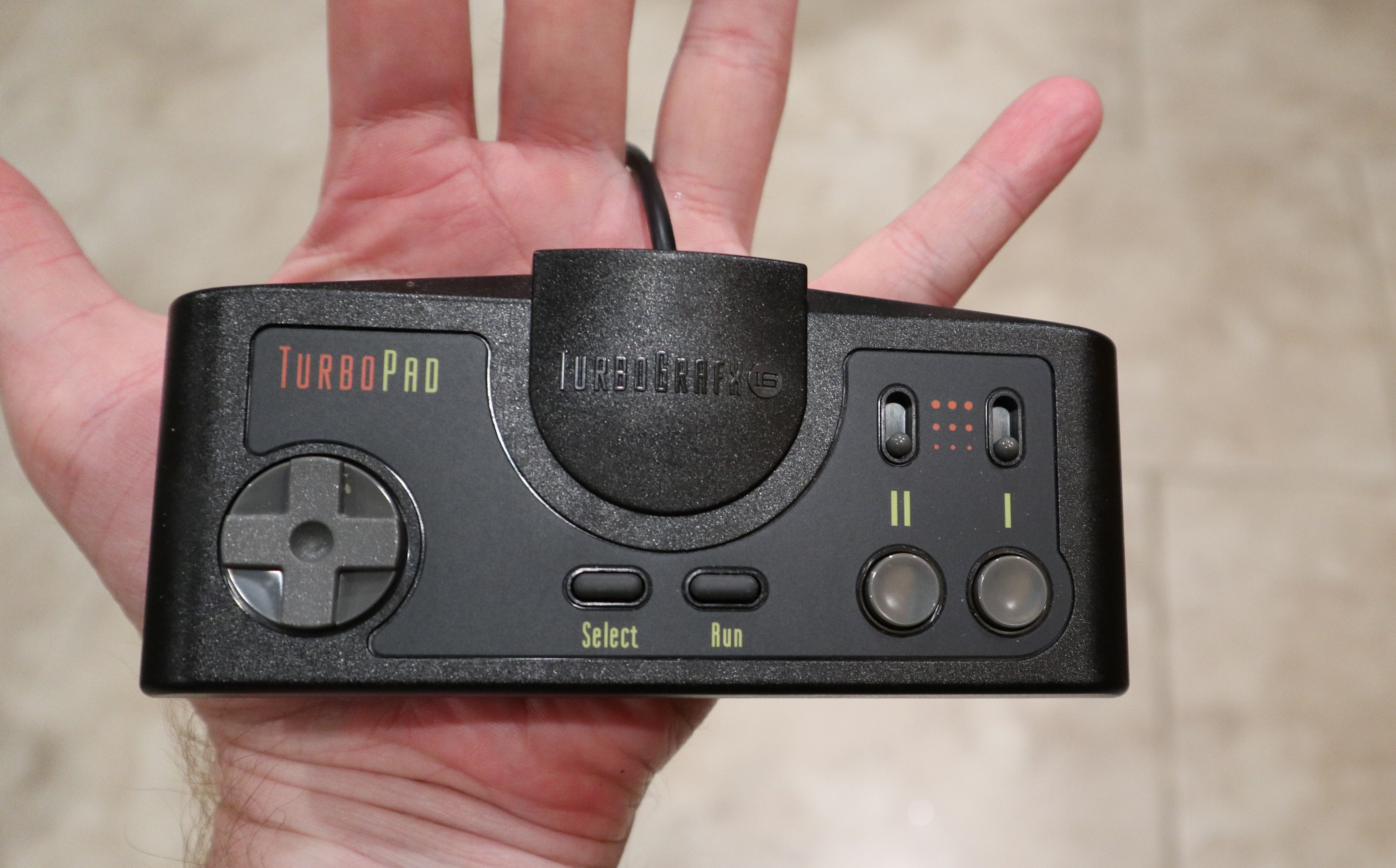 "The TG-16M's controller largely resembles the original, right down to the divots in its action buttons, the firm-yet-pliable d-pad, and, of course, those sweet, sweet ""turbo"" toggles."