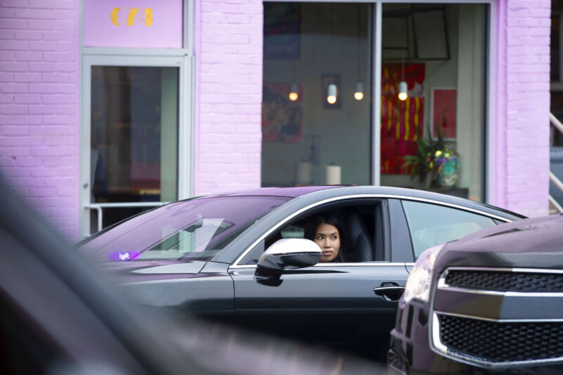 Promotional image of a Lyft driver waiting in her car.