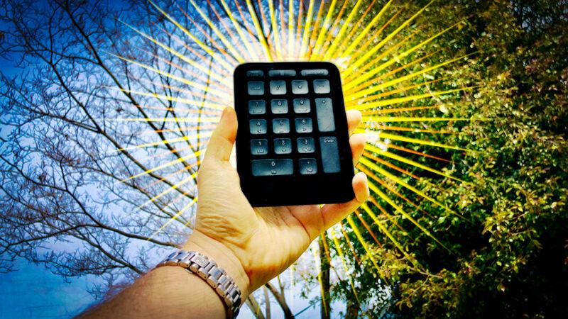 Stylized image of a hand holding a wireless 10-key pad.