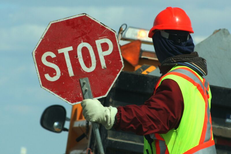 A construction worker holding a stop sign.