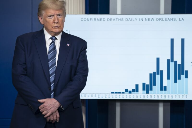 President Donald Trump at a press conference, standing in front of a chart showing the number of coronavirus deaths in New Orleans.