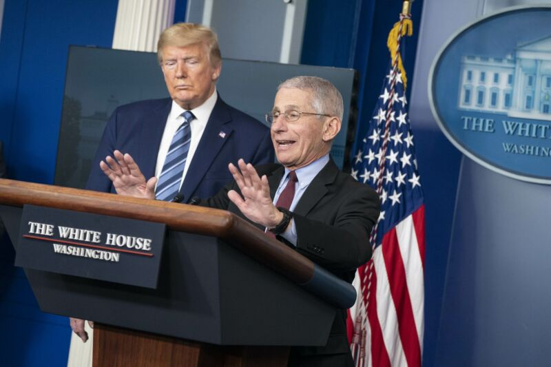 Anthony Fauci speaking at a podium during a press briefing while President Trump looks on.