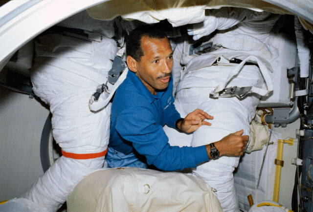Pilot Charles F. Bolden is surrounded by spacesuits in the airlock of Discovery during STS-31.