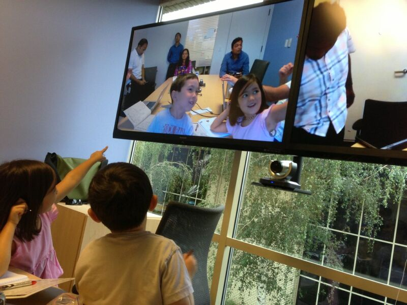Children take part in a video conference on a large TV.
