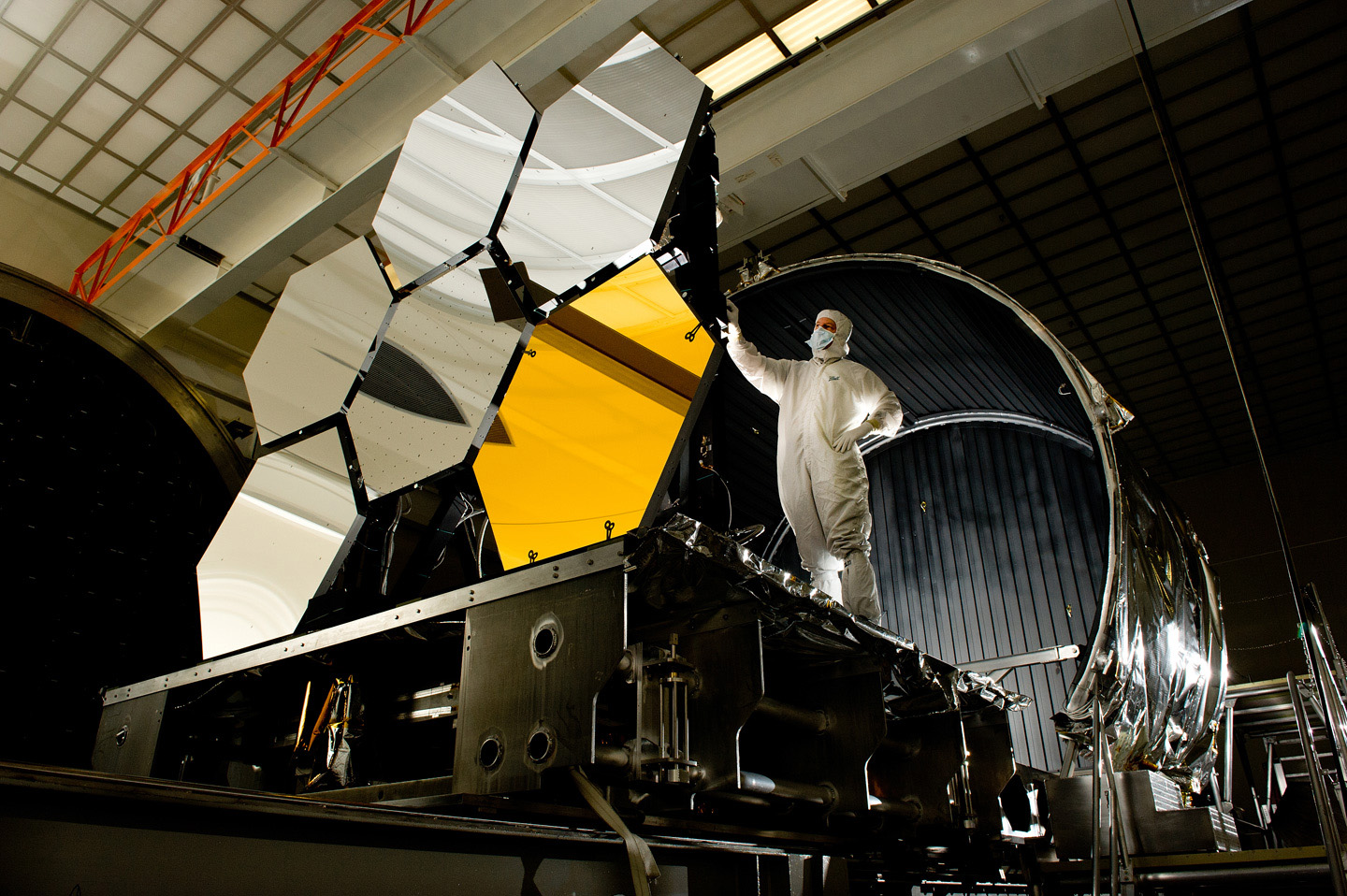Technician standing near some of the segments of the James Webb Space Telescope primary mirror.