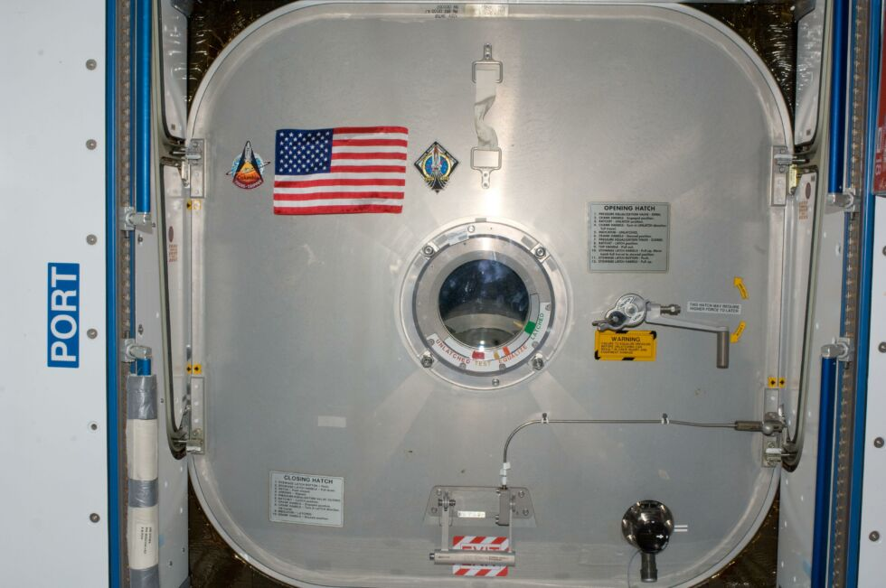 Inside the International Space Station's Node 2, the STS-135 crew presented the Expedition 28 crew this special US flag and mounted it on the hatch leading to Atlantis.