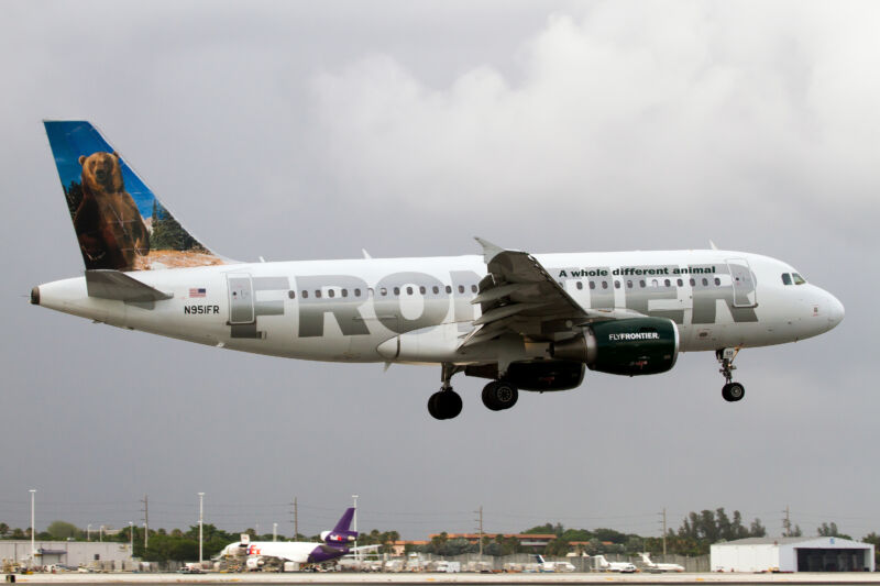 A passenger jet with the word Frontier emblazoned on it lifts off.