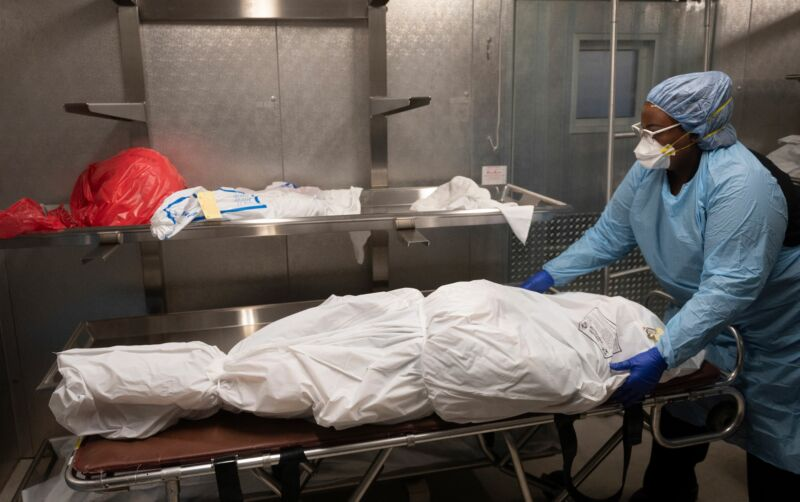 A medical technician wearing protective gear handles a dead body wrapped on a stretcher.
