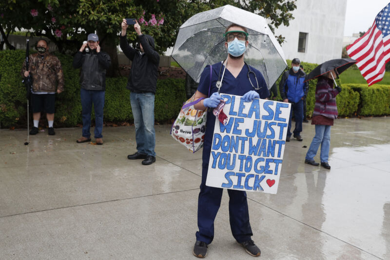 A masked man in OR scrubs holds a sign saying