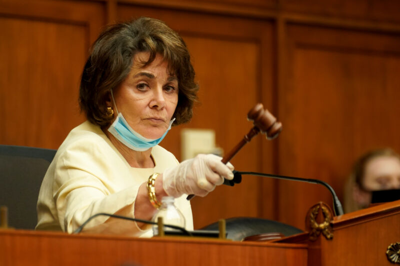 A serious woman in a suit raises a gavel.
