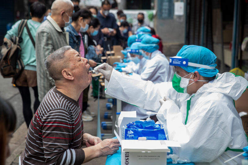 Medical workers take swab samples from residents (L) to be tested for the COVID-19 coronavirus, in a street in Wuhan in China