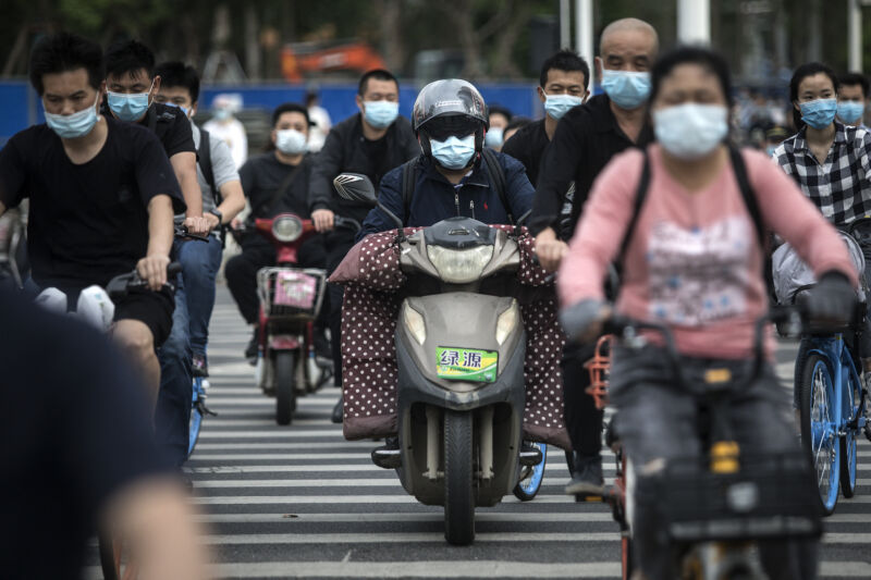 A road is full of masked people on scooters and bikes.