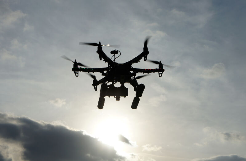 A drone in flight is silhouetted against a cloudy sky.