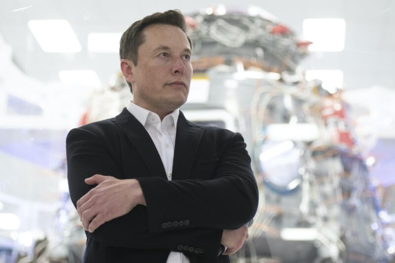 SpaceX CEO Elon Musk standing with his arms crossed.