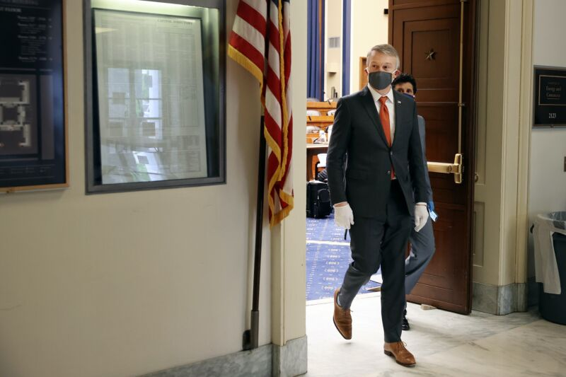 Rick Bright walks out of a hearing room, wearing a face mask and gloves.