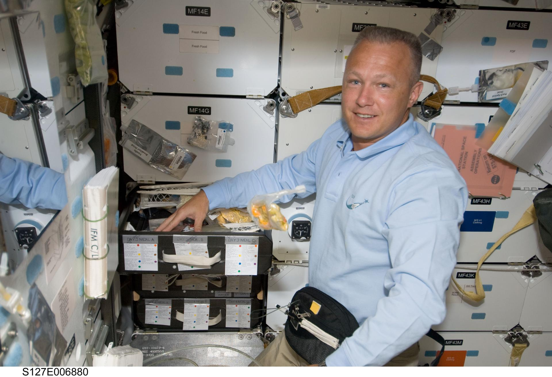 A younger Hurley on the space shuttle's mid deck on STS-127 in 2009.