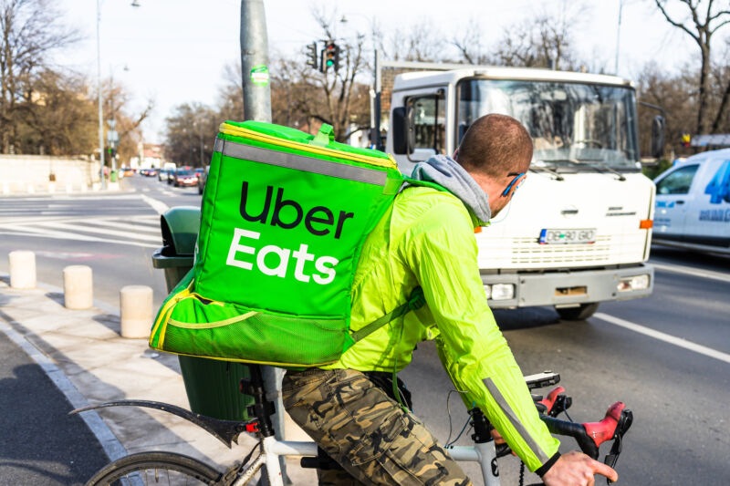 Young man on a bike with Uber Eats logo delivering food in Bucharest, Romania, 2020