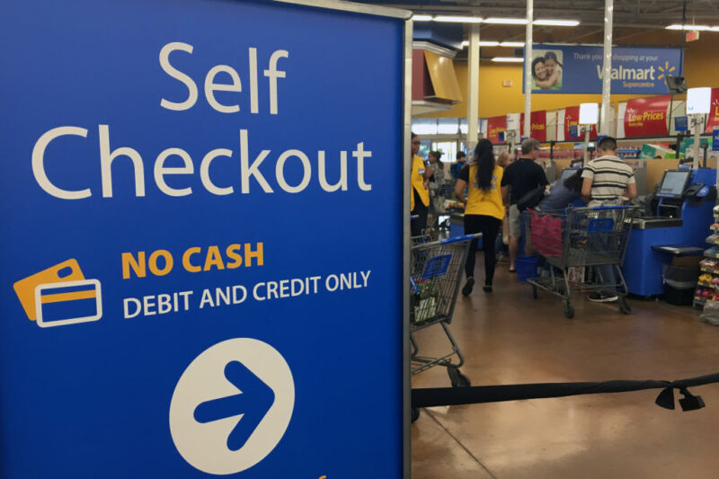 Customers and staff cluster around grocery store self-check lane.