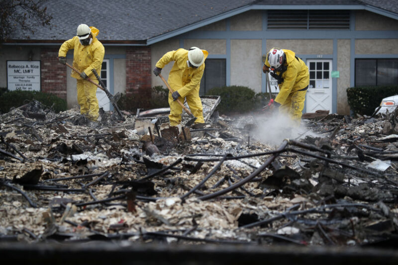 Search and rescue crews dig through the burnt remains of a business as they search for human remains on November 21, 2018 in Paradise, California. Fueled by high winds and low humidity, the Camp Fire ripped through the town of Paradise, charring over 150,000 acres.
