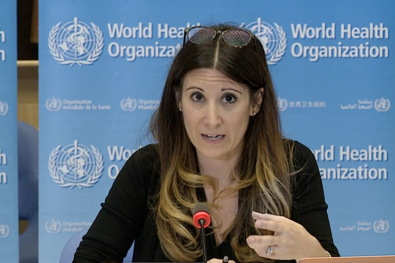A women speaks into a microphone in front of a World Health Organization logo.