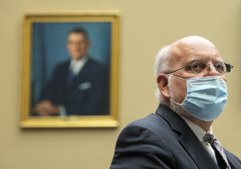 A serious man wears a suit and a face mask.