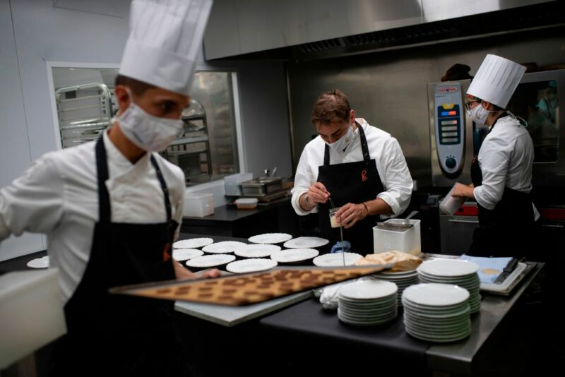 Masked chefs work in a professional kitchen.