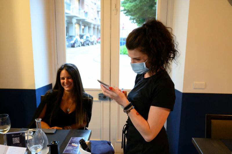 A waitress with protective mask at work among customers without one.