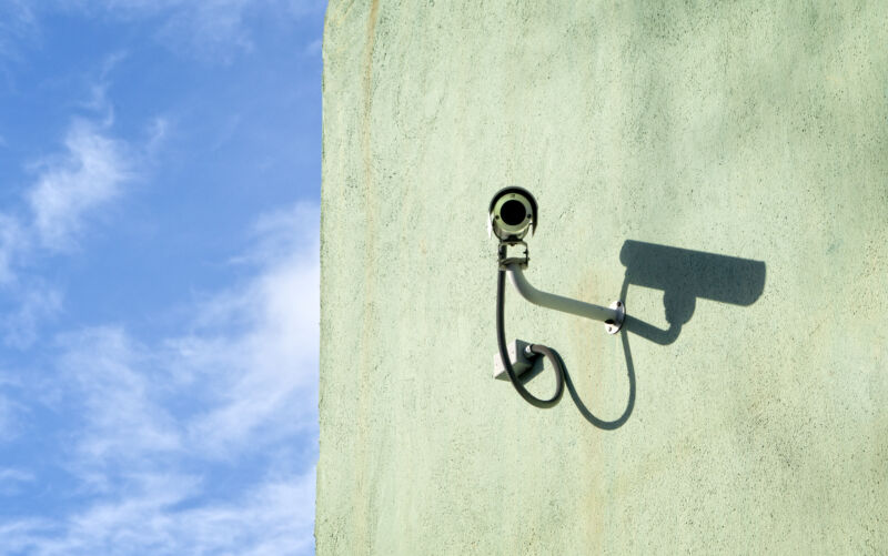 A surveillance camera mounted on a wall on a sunny day.