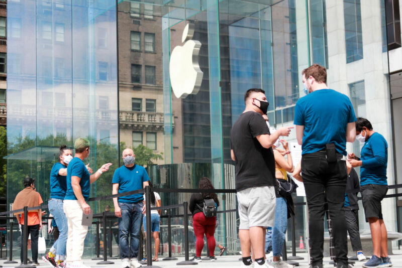 Masked people mill about the glass walls adorned with the Apple logo.