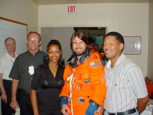 Tom Cruise wears a space shuttle-era Advanced Crew Escape Suit (ACES) pressure garment during a visit to the Jake Garn Simulator Facility at NASA's Johnson Space Center in Houston, Texas, in September 2002. Pictured with Cruise (left to right): astronaut Charlie Precourt, Bill Todd, Sharon McDougle, and George Brittingham.