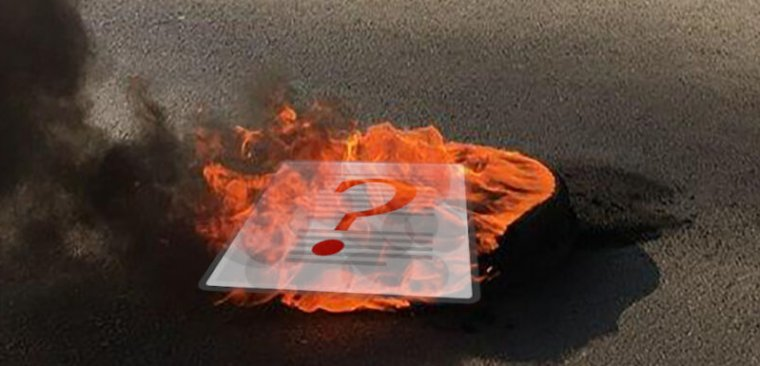 Photograph of a burning piece of paper on pavement.