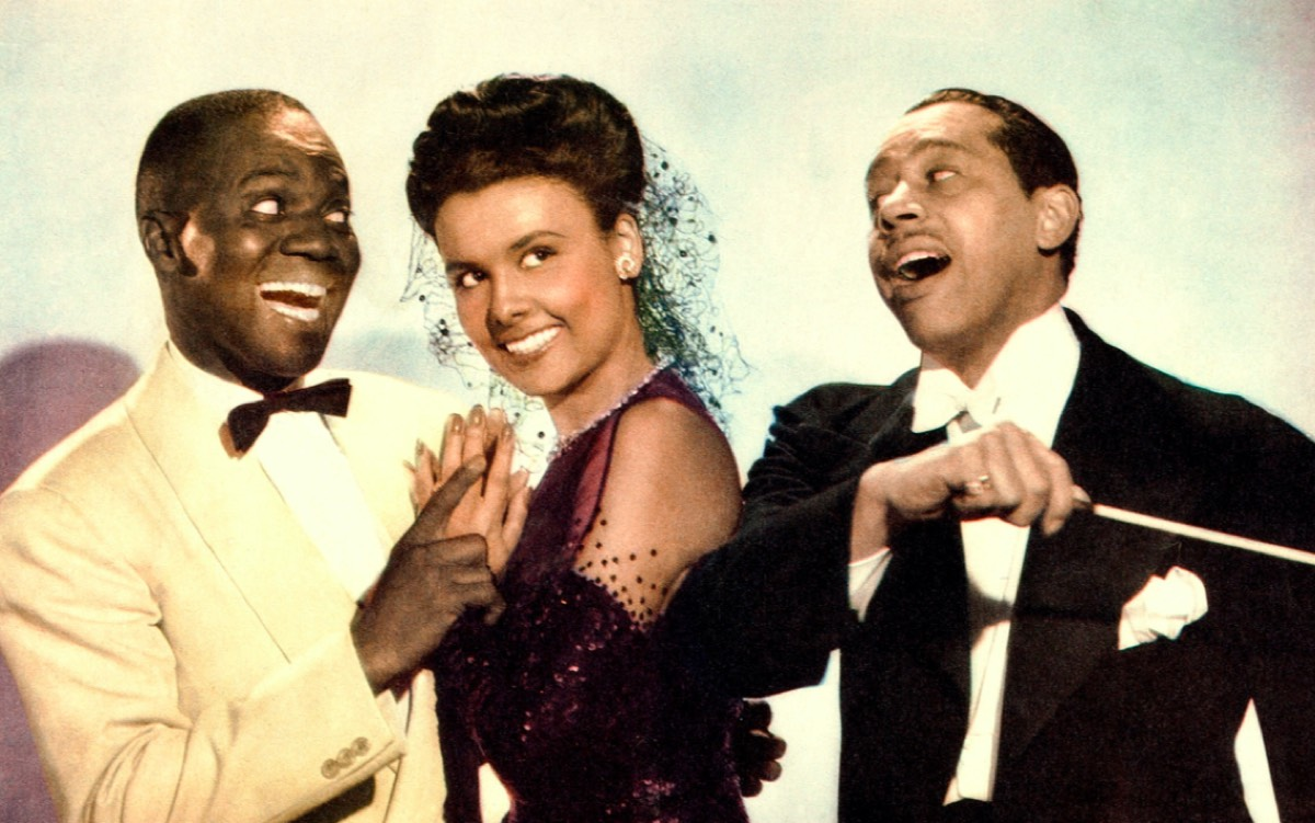 Bill Robinson as Bill Williamson, Lena Horne as Selina Rogers, and Cab Calloway as himself in the 1943 film <em>Stormy Weather.</em>