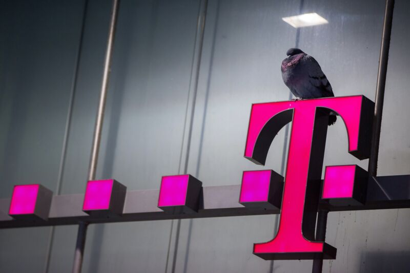 A bird sits on top of a T-Mobile sign outside a mobile phone store,