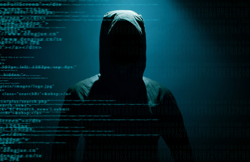 Stock photo of a hooded figure hiding behind computer code.