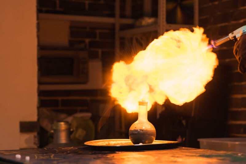 Lab technician setting fire to a ball with hydrogen blowtorch.