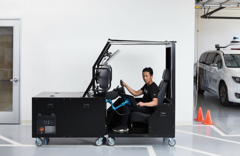A man operates an automobile simulator.